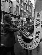 "Anti-smoking Campaign..1986..12.03.1986..03.12.1986..12th March 1986..In Grafton Street,Dublin,the anti-smoking campaign ""Unhooked A Cigarette Addict""from thre perils of smoking. Today,Wednesday,was declared 'National No Smoking Day""in order to heighten awareness...Pictured in Grafton,Street,Dublin,Mr Donal O'Shea,Chairman of the Health Education Bureau,in conjunction with students from The College Of Marketing and Design highlight the dangers of smoking.The students distributed fruit to passers by to give a healthy option to smoking...Note. Through the years Medical Science has determined that smoking is a major contributory factor in cancer and heart disease. With further research ""Passive smoking""(that is those in the vicinity of smokers but who do not smoke themselves) was also found to be detrimental to health..In March 2004 Ireland became the first country in the World to introduce a ban on smoking in the workplace,This included pubs,cinemas and public transport etc..In 2012 the anti smoking lobby is pushing for a complete ban on smoking in all public spaces and within the confines of private cars.."