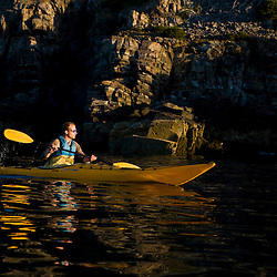 A man sea kayaking near Burnt Porcupine Island in Maine's Acadia National Park.  Bar Harbor.