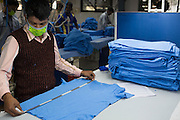 A man checks the measurements of a C & A T-shirt in a Pratibha Syntax factory, where organic cotton is being used to make clothes, Indore, India.