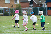 Four young children wearing sun hats take part in an egg and spoon race at a UK primary school.