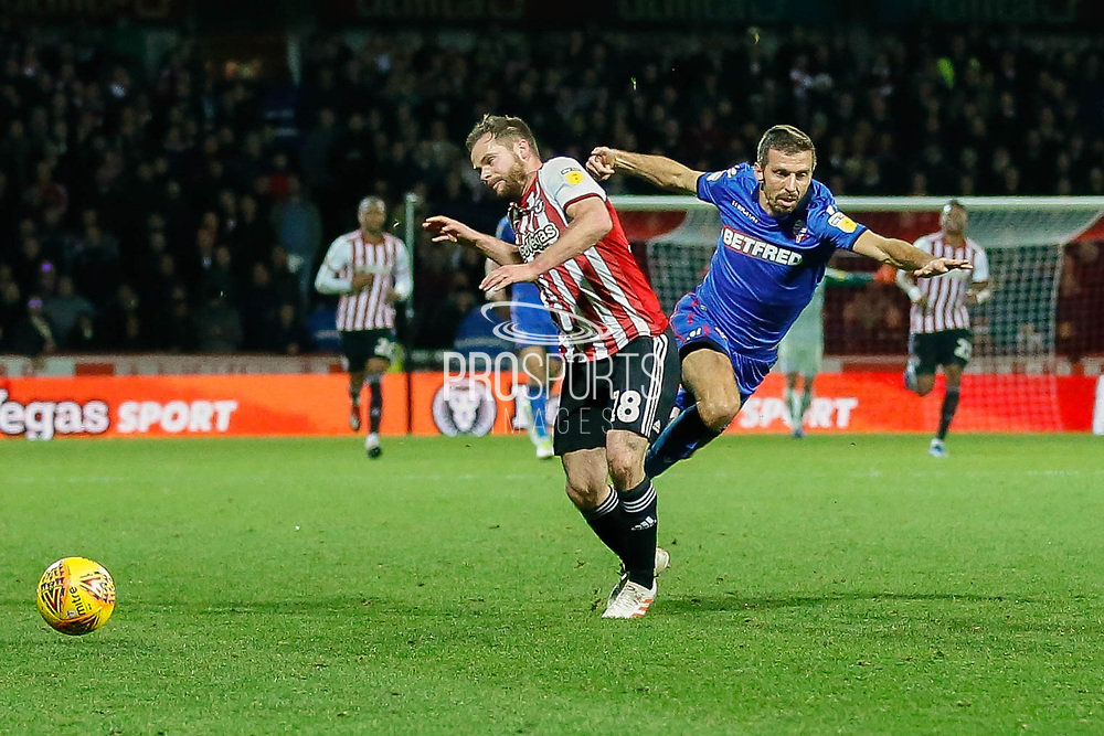 Brentford midfielder Alan Judge (18) battling with Bolton Wanderers midfielder Gary O'Neil (19), a challenge that sparked a clash between the payers of both sides and a huge reaction from the fans, during the EFL Sky Bet Championship match between Brentford and Bolton Wanderers at Griffin Park, London, England on 22 December 2018.
