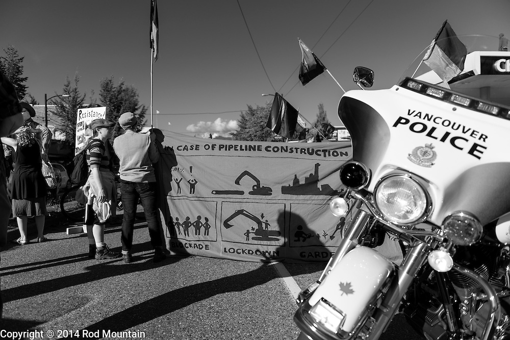 Vancouver, BC, Canada - September 27, 2014 - A Police motorcycle is parked to block part of the street as a crowd gathers at a Chevron gas station for the &quot;Party Against the Pipelines&quot; Protest in Vancouver, B.C. <br />