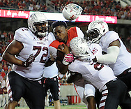 Houston quarterback Greg Ward Jr., center, loses his helmet after being tackled by Temple linebacker Avery Williams (2) and defensive lineman Hershey Walton (72) during the first half of a college football game, Friday, October 17, 2014, at TDECU Stadium in Houston.