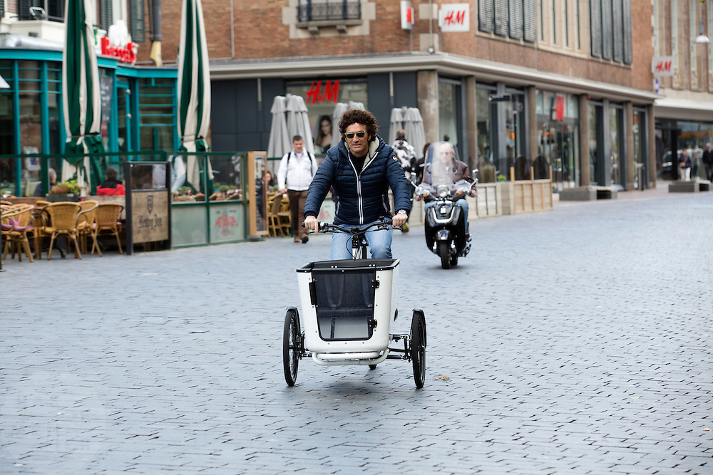 In Nijmegen fietst een man met een bakfiets door het centrum. Bakfietsen worden in heel Europa steeds vaker ingezet, zowel door particulieren als bedrijven. Het is een duurzame vorm van transport en biedt veel voordelen.<br /> <br /> In Nijmegen a man cycles downtown on a cargo bike. Cargo bikes are increasingly being deployed across Europe, both individuals and businesses. It is a sustainable form of transport and offers many advantages.