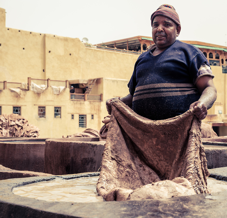 FEZ, MOROCCO - CIRCA APRIL 2017:  Man working in the Fez tannery dyeing leather.