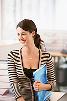 Mid-adult female office worker leaning on cubicle holding files