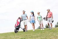 Friends talking while walking at golf course against clear sky
