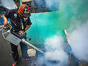 02 DECEMBER 2015 - BANGKOK, THAILAND:  A health department mosquito control worker sprays homes and businesses in a neighborhood in Bangkok. The Public Health Ministry in Thailand said that more than 111,000 cases of dengue fever have been reported in 2015, an increase of more than 200% over the number of cases of dengue fever reported 2014. Dengue fever is a virus spread by mosquito and is endemic in southeast Asia. Thai health officials are aggressively spraying areas where mosquitoes are known to live and leading public information and education sessions on preventing dengue fever. There is no vaccine for dengue fever, so preventing dengue means avoiding mosquitoes.       PHOTO BY JACK KURTZ
