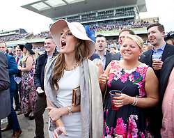 LIVERPOOL, ENGLAND - Friday, April 4, 2014: Racegoers cheer their horse on during Ladies' Day on Day Two of the Aintree Grand National Festival at Aintree Racecourse. (Pic by David Rawcliffe/Propaganda)