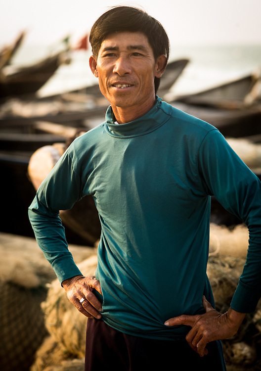 Shrimp fisherman stops to pose outside Ky Anh, Vietnam with his his boat in the background