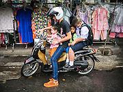 30 MAY 2013 - BANGKOK, THAILAND:     A man and his children on his motorcycle on Krung Kasem Road in Bobae Market in Bangkok. Bobae Market is a 30 year old famous for fashion wholesale and is now very popular with exporters from around the world. Bobae Tower is next to the market and  advertises itself as having 1,300 stalls under one roof and claims to be the largest garment wholesale center in Thailand.  PHOTO BY JACK KURTZ