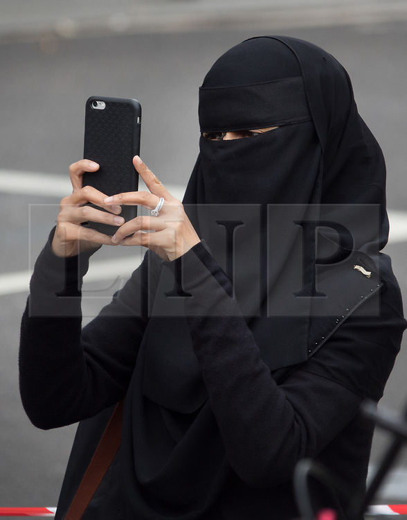 © Licensed to London News Pictures. 11/10/2017. London, UK. A woman dressed in a traditional burka takes a phone photograph as Syrian women sing the chimes of Big Ben on a double decker bus in Parliament Square decorated with photographs of their family members missing in the Syrian war. Families for Freedom campaign for the rights of the missing in Syria. Big Ben will miss 200,000 of its bongs, the same number that are are estimated to be in prison in Syria  Photo credit: Peter Macdiarmid/LNP