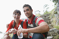 Man holding water bottle embracing woman on steps portrait
