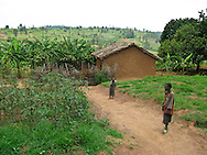 Rwanda- A pair of children walk along the pathway past a house in the community surrounding the Gary Scheer school, the Southern Province, Rwanda.