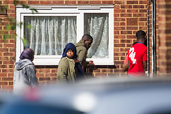 Apparent mourners gather on the estate where a 24 year old male known locally as Mali died at the scene of yet another murder, this time on an estate on Crows Road in Barking, London, May 18 2018.