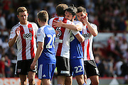 Ipswich midfielder Jonathan Douglas (22) hugging Brentford defender Harlee Dean (6)  during the EFL Sky Bet Championship match between Brentford and Ipswich Town at Griffin Park, London, England on 13 August 2016. Photo by Matthew Redman.