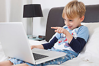 Playful Caucasian boy using laptop computer in bed
