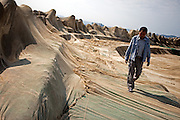 Korean man walking beside the wave-breaks at Bukbu beach / Pohang, South Korea, Republic of Korea, KOR, 04 October 2009:
