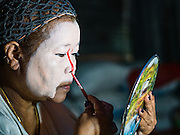 04 OCTOBER 2016 - BANGKOK, THAILAND:  A Chinese opera performer puts on her makeup beneath stage at the Vegetarian Festival at the Chit Sia Ma Chinese shrine in Bangkok. The Vegetarian Festival is celebrated throughout Thailand. It is the Thai version of the The Nine Emperor Gods Festival, a nine-day Taoist celebration beginning on the eve of 9th lunar month of the Chinese calendar. During a period of nine days, those who are participating in the festival dress all in white and abstain from eating meat, poultry, seafood, and dairy products. Vendors and proprietors of restaurants indicate that vegetarian food is for sale by putting a yellow flag out with Thai characters for meatless written on it in red.    PHOTO BY JACK KURTZ