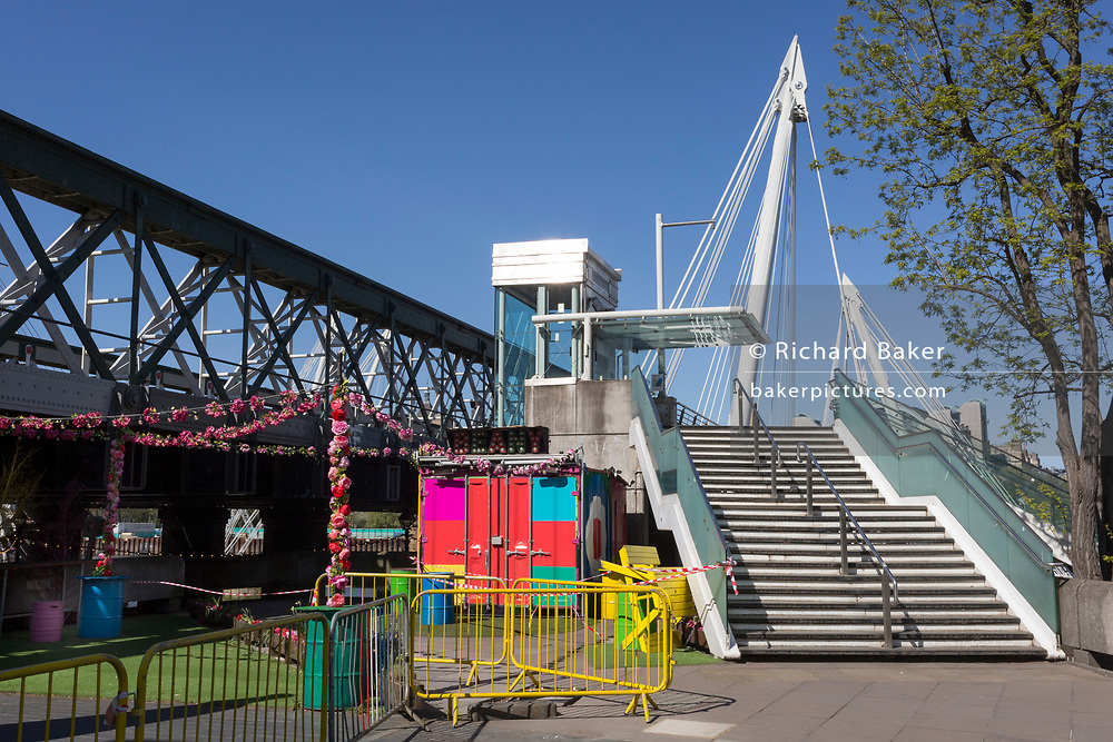 At the beginning of the fourth week of the UK government's lockdown during the Coronavirus pandemic, and with 120,067 UK reported cases with 16,060 deaths, hazard tape has closed an empty landscape of outdoor cafe benches with the steps leading up to Hungerford Bridge on the capital's Southbank in South London, on 20th April 2020, in London, England.