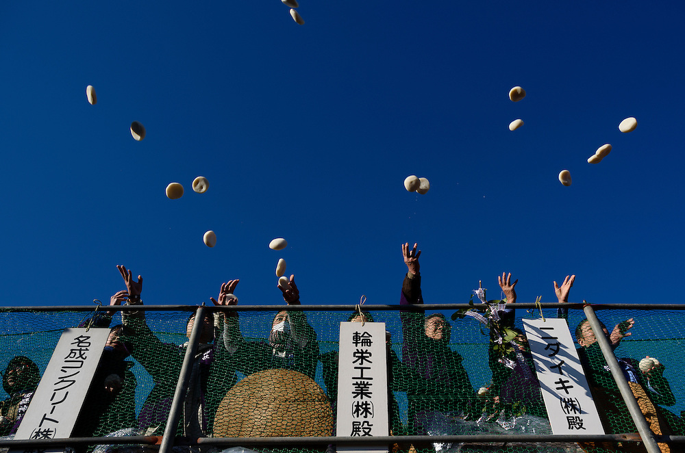 People throw rice cakes to a crowd below during Honen-sai, a fertility festival at Tagata Shrine in Komaki, Aichi Prefecture, Japan. The traditional Shinto festival celebrates fertility and a bountiful harvest.