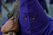 A hooded penitent carries a heavy wooden cross through the city streets during the Procession of Silence as part of Holy Week March 30, 2018 in Querétaro, Mexico. The penitents, known as Nazarenes, carry heavy crosses and drag chains in a four hour march to recreate the pain and suffering during the passion of Christ.