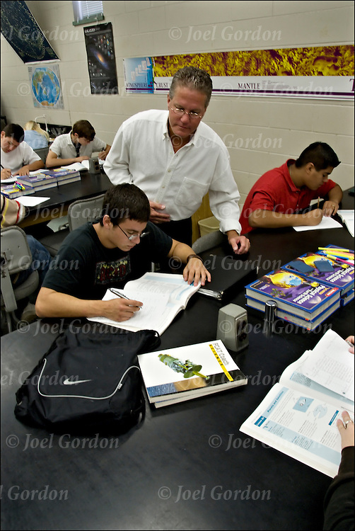 9th grade Earth / Space Science class, teacher among students desks writing, books open,concentrating on vocabulary leason using 4 column notes with the following headings: word, definition, examples, sentence-graphic.