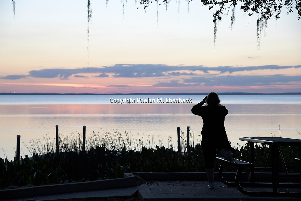 A visitor watches a sunset over Lake Apopka from a boat dock at Magnolia Park, Monday, Jan. 16, 2017, in Apopka, Fla. (Photo by Phelan M. Ebenhack)