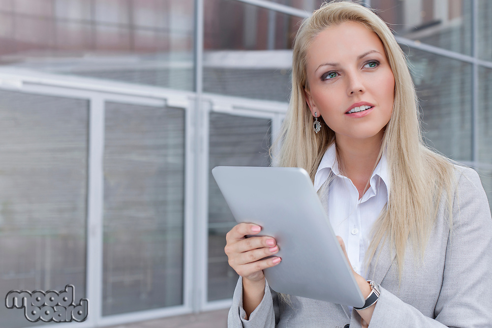 Thoughtful young businesswoman using digital tablet while looking away against office building