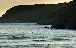 © Licensed to London News Pictures.23/07/2012. Caswell Bay, Gower Peninsula, Swansea, Wales, UK. A lone surfer paddles his board on the last waves of the day off Caswell Bay. Photo credit : Dave Warren/LNP