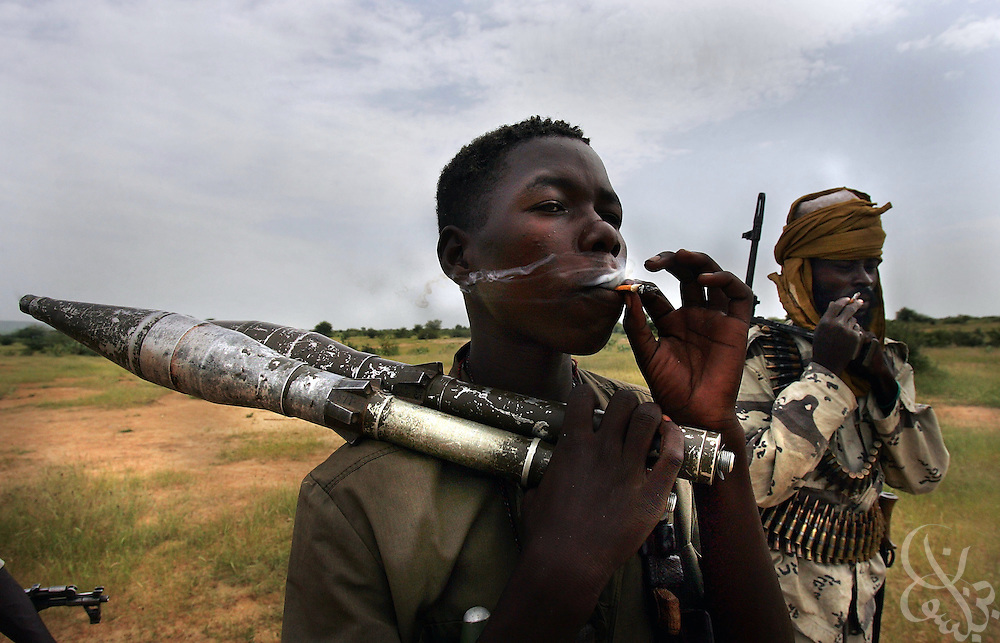 MISTEREI, SUDAN- SEPTEMBER 08:  Heavily armed rebel fighters from the Sudanese Justice and Equality Movement (JEM)  smoke one of their 5 rationed cigarettes (per every several days) at their base in the Darfur region of Sudan 08 September, 2004. Both rebel groups, the JEM, and the Sudanese Liberation Movement (SLM) continue to abide by a current ceasefire and are participating in talks with the Sudanese government in neighboring Nigeria, but are growing increasingly frustrated by the lack of progress and warn of an impending resumption of military action if the situation in Darfur does not improve dramatically within the next weeks.