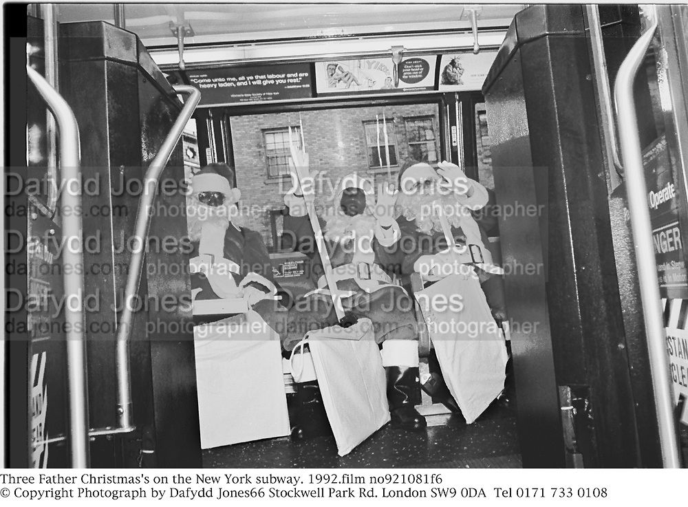 Three Father Christmas's on a New York bus. 1992.film no921081f6<br />© Copyright Photograph by Dafydd Jones<br />66 Stockwell Park Rd. London SW9 0DA<br />Tel 0171 733 0108
