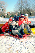 African American and friends age 12 riding snow tubes and sleds in winter.   St Paul  Minnesota USA