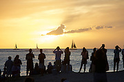 Tourists enjoying the sunset at Waikiki Beach.