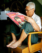 A man reads a paper. Aung San Suu Kyi since her liberation has been active on the NLD electoral campaign. Excluded for years, she is now regularly on the front pages. Yangon, Myanmar. 2012
