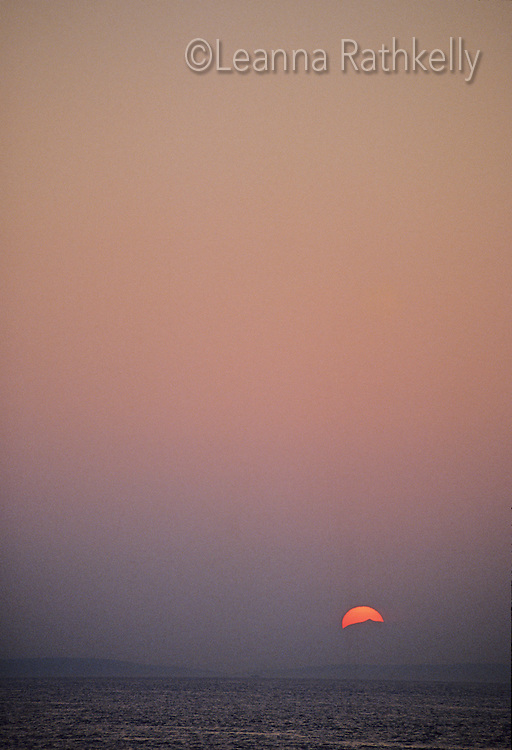 The sun sinks into a mountain top of Vancouver Island.
