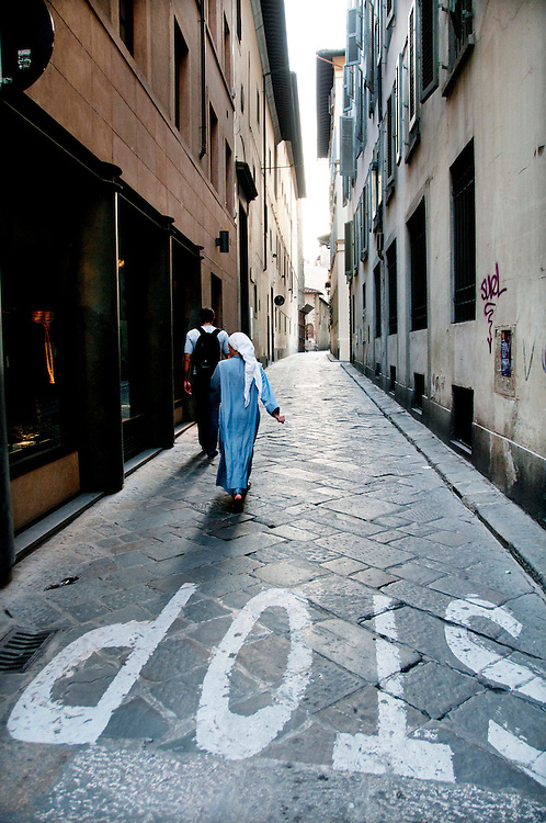 A Caucasian man and a Muslim woman walking on Via De Ramaglianti, a small, stone street in an alley way in Florence, Italy. The word stop is written on the street. The woman is wearing traditional Muslim hijab, a white head scarf and a blue, dress that goes to her ankles.
