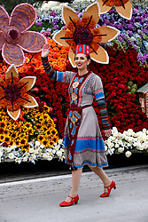 A woman waves next to a float on the route of the 2017 Tournament of Roses Parade, Rose Parade, Pasadena, California, United States of America