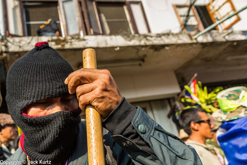 17 JANUARY 2014 - BANGKOK, THAILAND:  An anti-government protestor armed with a club looks for assailants who threw an IED at an anti-government rally. The attackers were not found but officials claim to have found a weapons cache in an abandoned building nearby. Friday was day 5 of the anti-government Shutdown Bangkok protests. The protest, led by the People's Democratic Reform Committee, is calling for the suspension of elections pending political reform in Thailand. There was violence at several sites in Bangkok Friday, including running battles between government opponents and supporters at one site and an IED attack by unknown assailants on anti-government protestors at another site.   PHOTO BY JACK KURTZ