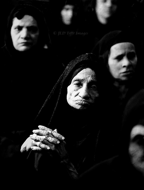 Aged women at a meeting in Cairo.  Image focus is on the folded fingers and steady gaze of a wrinkled and ancient female, surrounded by 5-6 others who are blurred but whose faces form a frame around her.