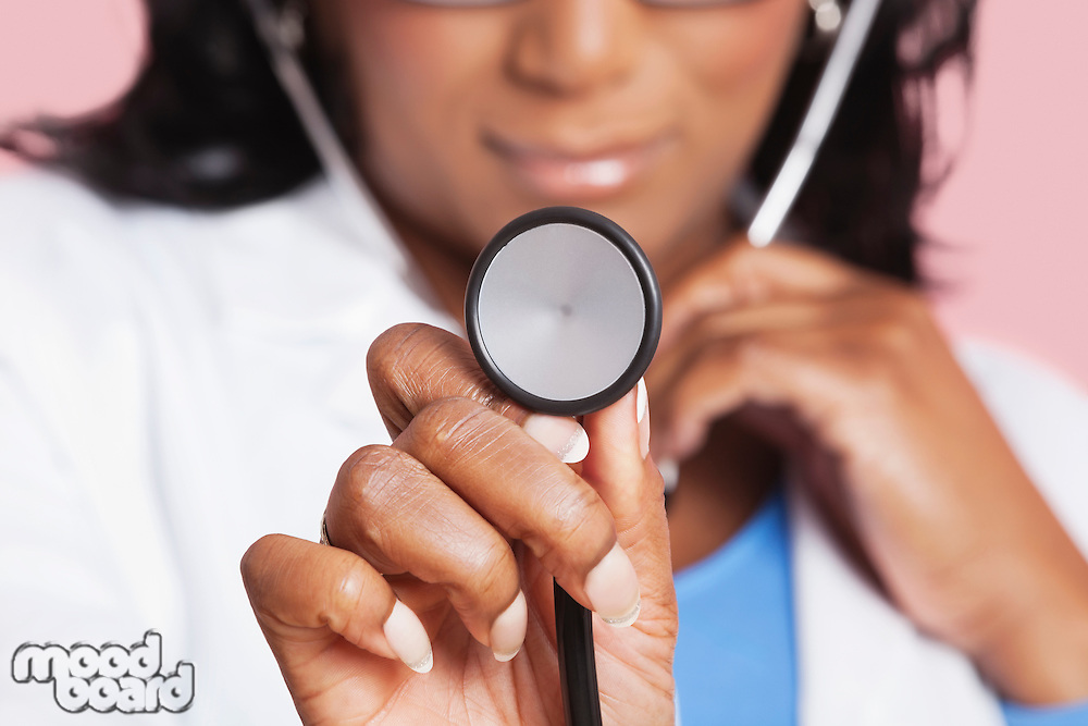 Close-up of female doctor holding stethoscope over pink background