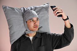 """© Licensed to London News Pictures. 29/10/2019. LONDON, UK. A staff member wears """"Pillowig"""", 2005, by JooYoun Paek, a design to allow users to nap anywhere. Preview of """"24/7: A Wake-Up Call For Our Non-Stop World"""", a new exhibition opening on 31 October at Somerset House.  The show examines our inability to switch off from our 24/7 culture.  Over 50 multi-disciplinary works explore the pressure to produce and consume information around the clock. taking visitors on a 24-hour cycle from dawn to dusk through interactive installations.  Photo credit: Stephen Chung/LNP"""