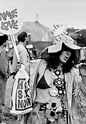 Lady wearing hat bikini and hippy necklaces, holds make love sign. Glastonbury 1994