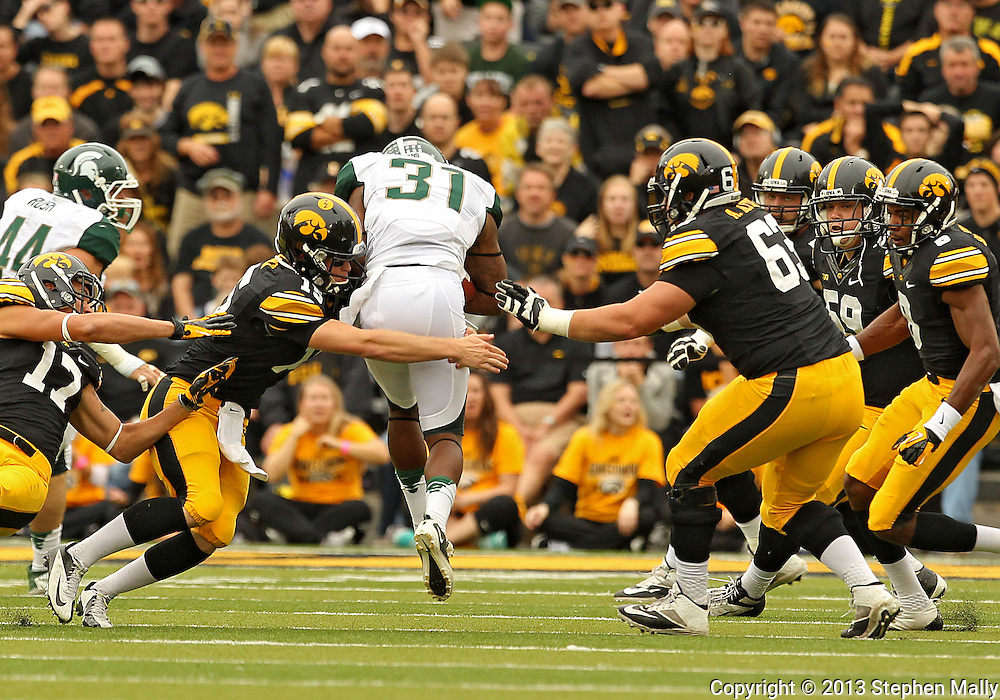 October 6 2013: Iowa Hawkeyes quarterback Jake Rudock (15) tackles Michigan State Spartans cornerback Darqueze Dennard (31) after Dennard's interception during the first quarter of the NCAA football game between the Michigan State Spartans and the Iowa Hawkeyes at Kinnick Stadium in Iowa City, Iowa on October 6, 2013. Michigan State defeated Iowa 26-14.