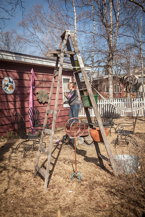 Neighbor Sharron Rooths arranges her eclectic front yard in Anchorage's South Addition neighborhood.