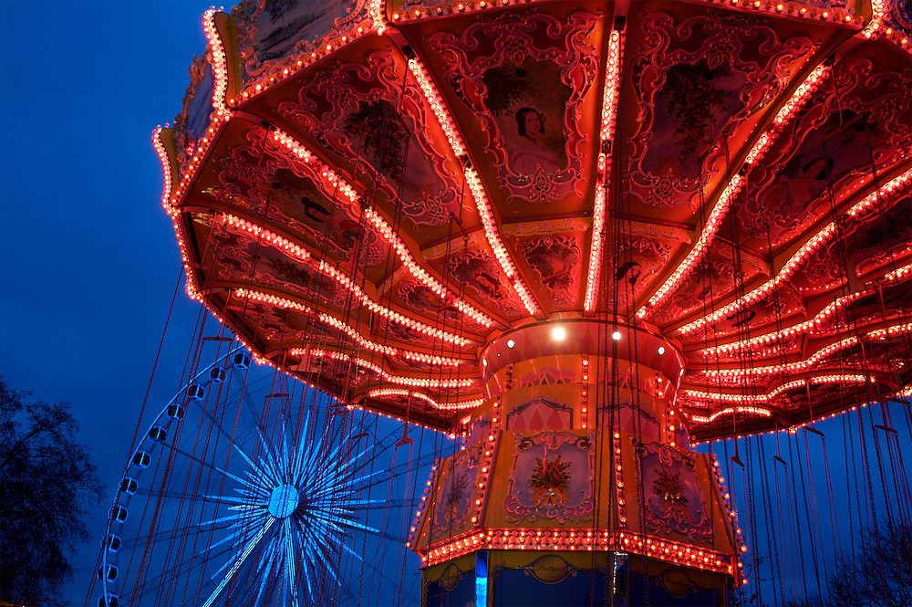 A red carousel and big wheel at Winter Wonderland,London.