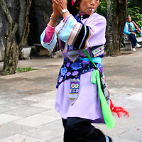 Asia, China, Kunming. Ethnic minority female dances at the Stone Garden in traditional dress.