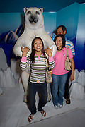 Siam Ocean World aquarium at Siam Paragon shopping center. Special Arctic exhibition. Visitors taking souvenir photos with a plastic polar bear.