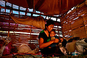 Kachin refugee housewives ai Je Yang Hka near China Myanmar boarder Lai Za. A refugee housewife sewing her son's clothes.
