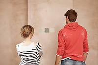 Couple choosing sample paint colours on wall back view